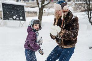 コートを着た大人と子供と雪