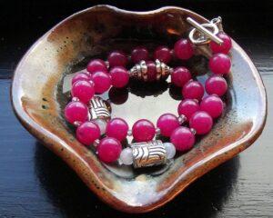 皿にのせられたピンクの翡翠の数珠