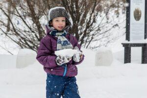 雪の中立つコートを着た子供