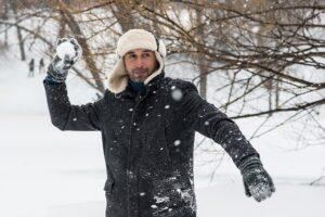 雪玉を投げようとしているコートを着た男性