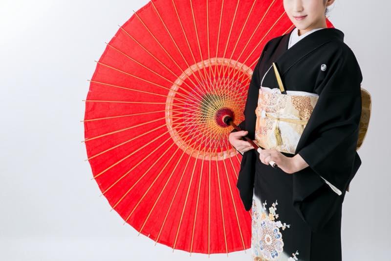 赤い傘をさす黒留袖の女性